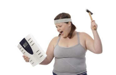 Angry fat woman with hammer and scale